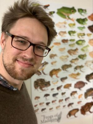 Image of Mark beside his poster showing some of the frogs of Madagascar to scale